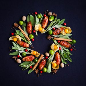 Festive wreath made from pigs in blankets herbs sprouts and spices