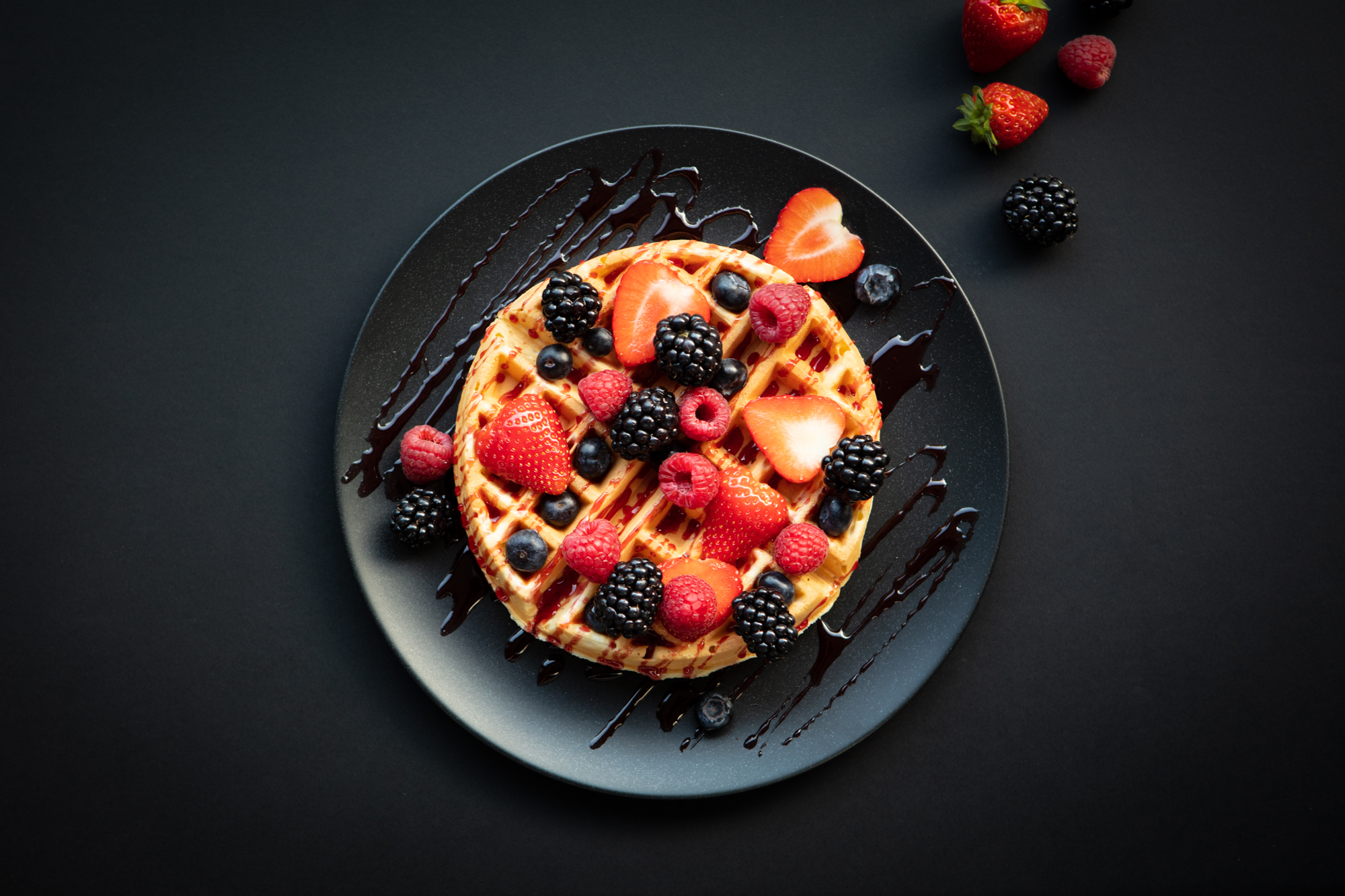 freshly made waffle topped with fresh fruit and fruit sauce