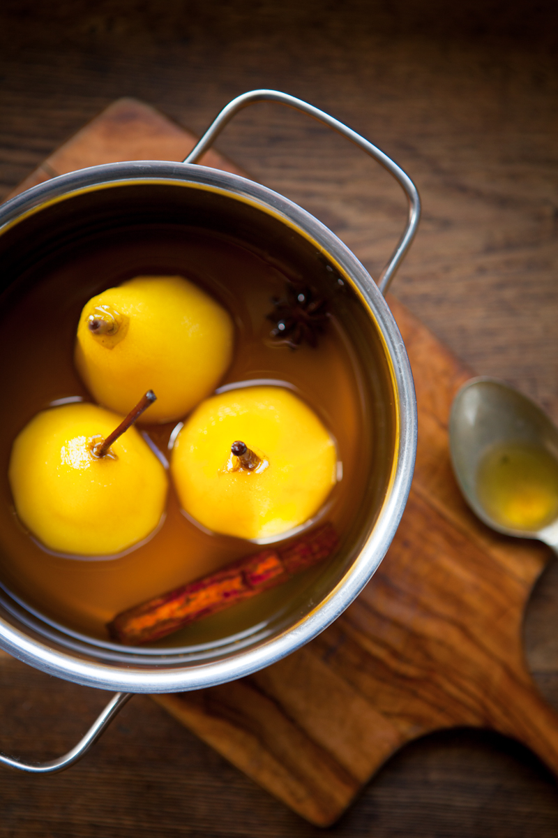 Poached pears in pan on chopping board